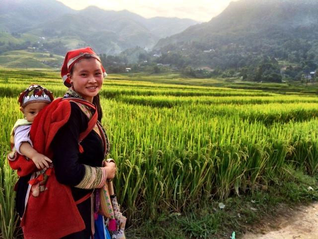 Mãe da tribo Red Dao caminha com o filho pelo pequeno vilarejo